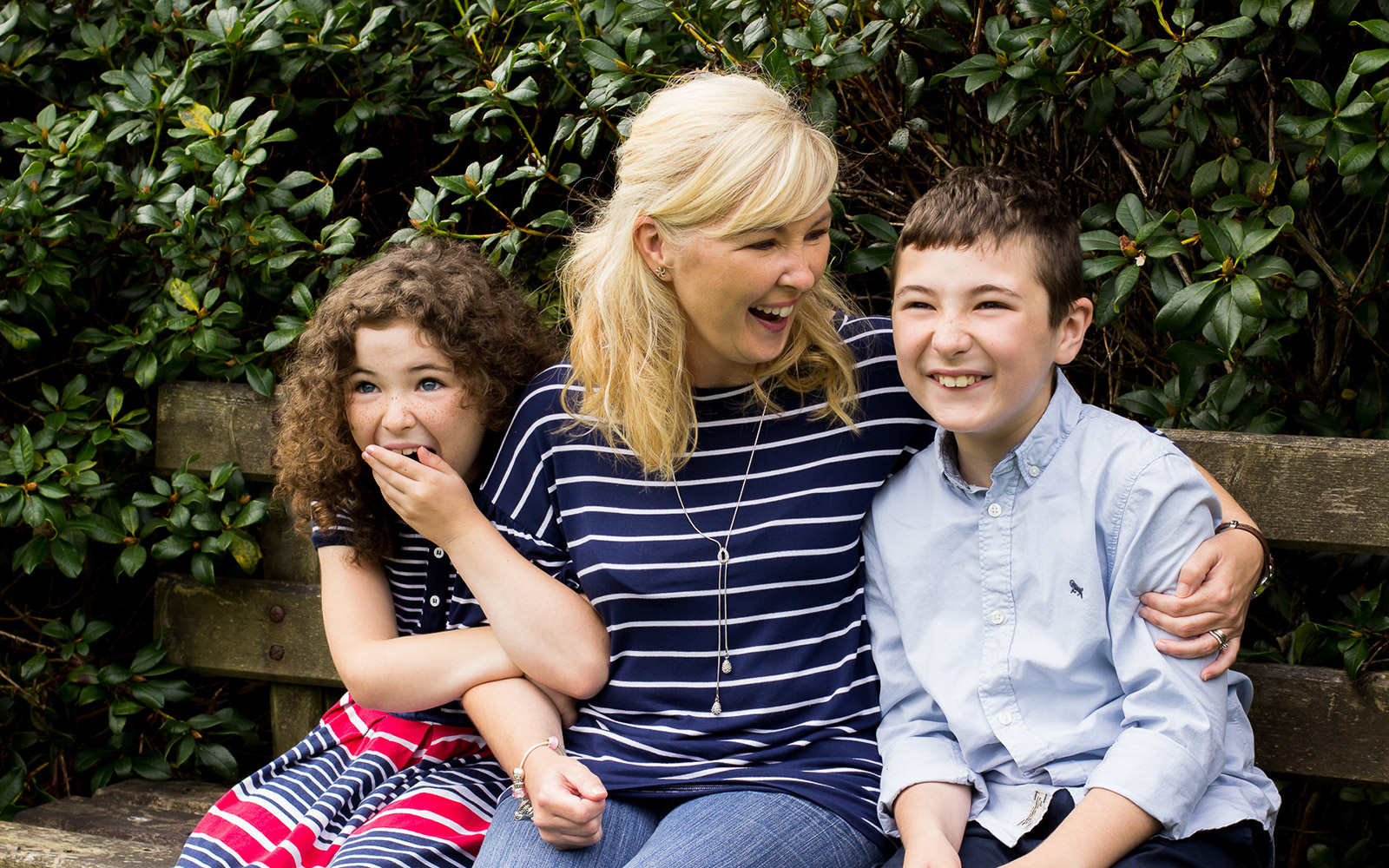 Mel Hudson Family Photography Belfast, Mum, son & daughter sitting on a park bench smiling and laughing