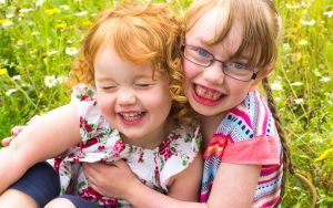 Mel Hudson Family Photography Belfast, two sisters giggling and cuddling