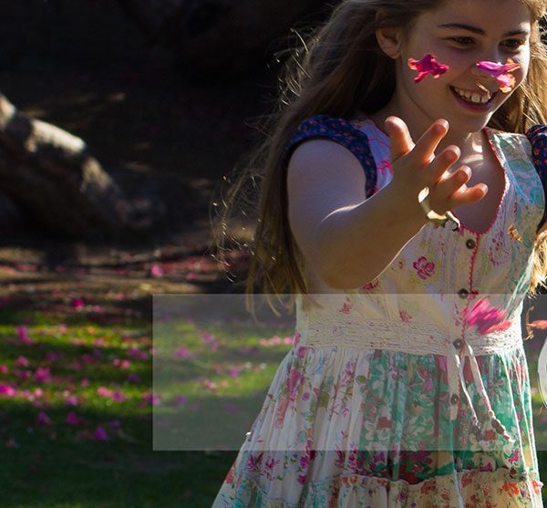 Mel Hudson Family Photography Belfast, young girl throwing petals in a fountain
