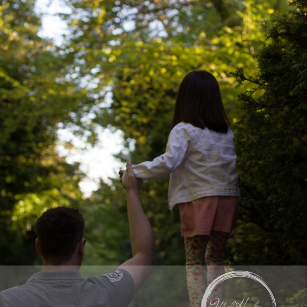 Mel Hudson Family Photography Belfast, young girl holding daddy hand as she's walking on a wall