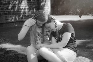 photograph of sisters stealing a moment, mel hudson experienced family photographer Northern Ireland