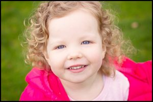 Little girl smiling into the camera at a family shoot with Mel Hudson Photography Belfast