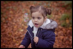 Little girl playing with the Autumn Leaves at Belfast family photo shoot
